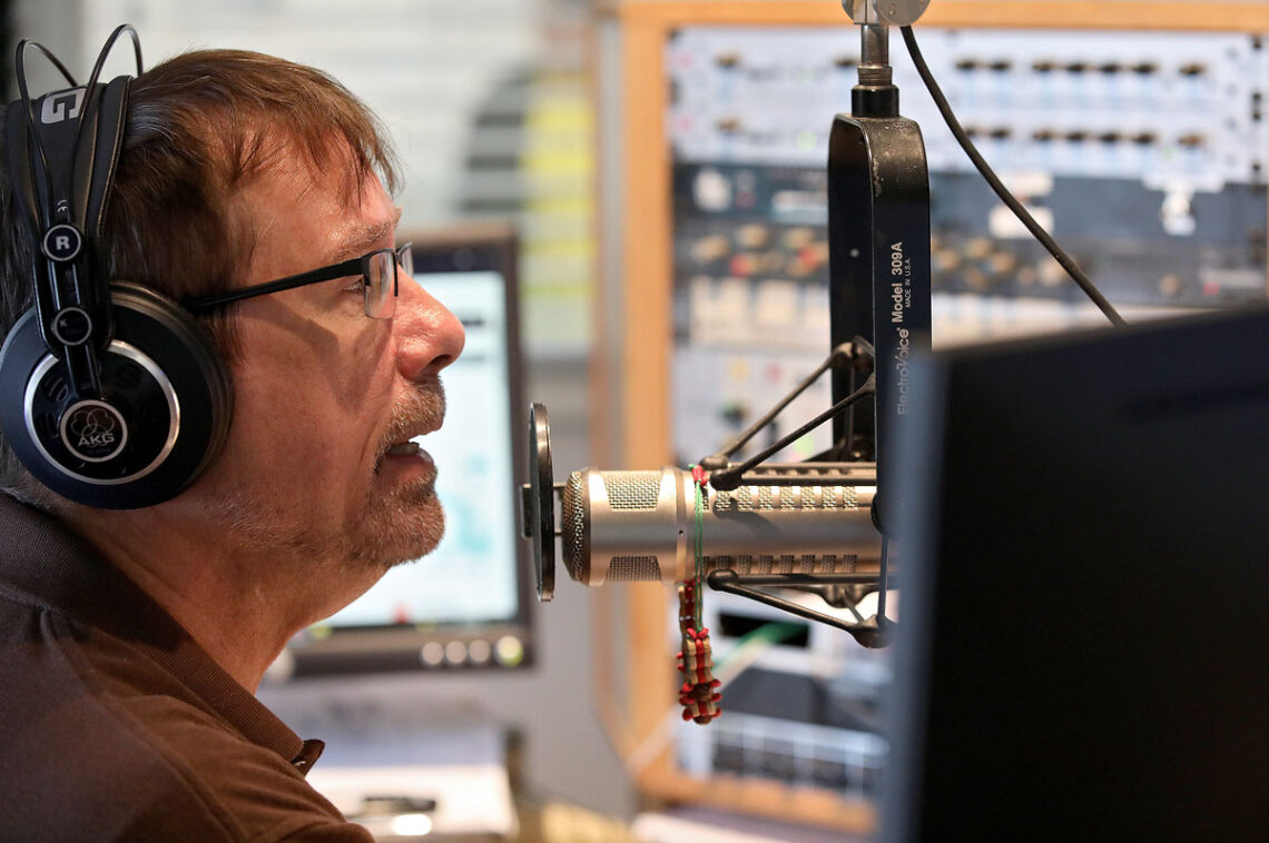 WXGM radio station disk jockey Harvey King on the air at the Gloucester radio strain delivering local content and news.
